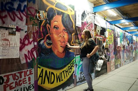 A woman pays homage as she touches a Breonna Taylor mural
